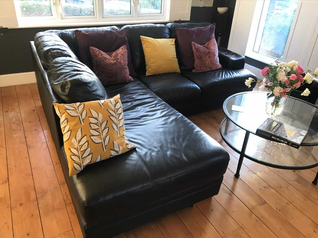 Leather corner sofa and foot stool.